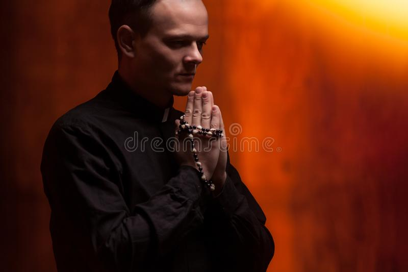 Stående av den stiliga katolska prästen eller pastorn med hundhalsbandet, mörker - röd bakgrund royaltyfria bilder