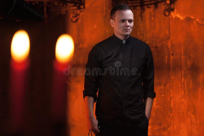 Stående av den stiliga katolska prästen eller pastorn med hundhalsbandet, mörker - röd bakgrund arkivbilder