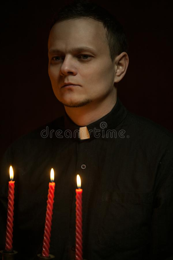 Stående av den stiliga katolska prästen eller pastorn med hundhalsbandet, mörker - röd bakgrund royaltyfria foton