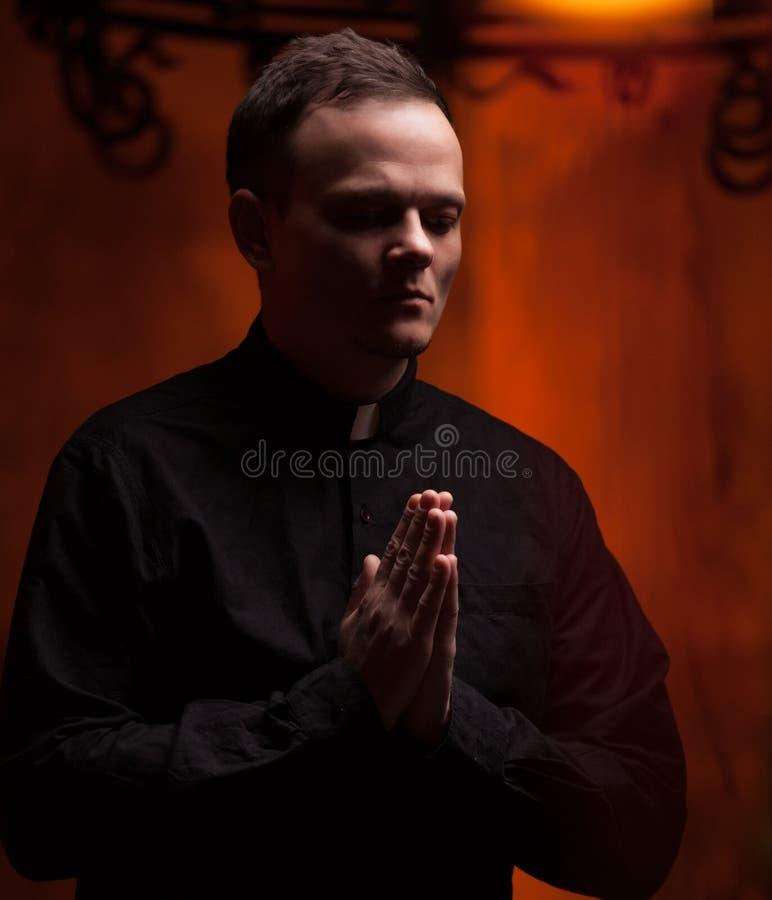 Stående av den stiliga katolska prästen eller pastorn med hundhalsbandet, mörker - röd bakgrund fotografering för bildbyråer