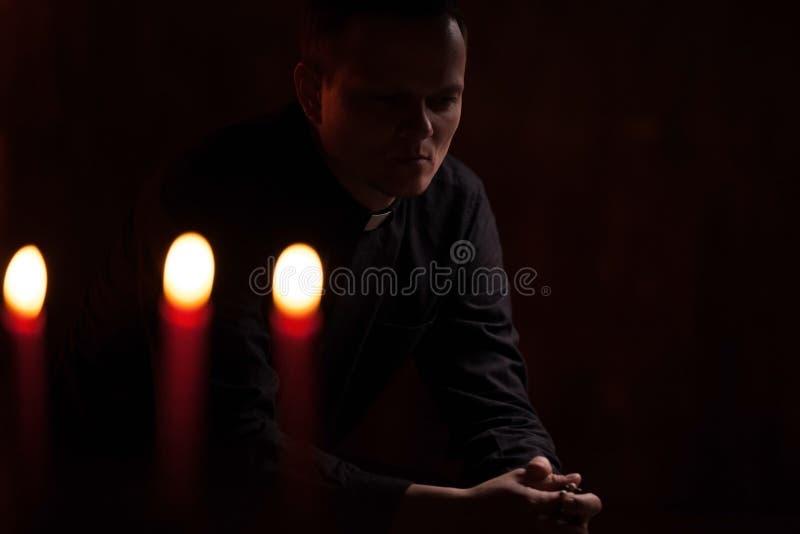 Stående av den stiliga katolska prästen eller pastorn med hundhalsbandet, mörker - röd bakgrund arkivfoto