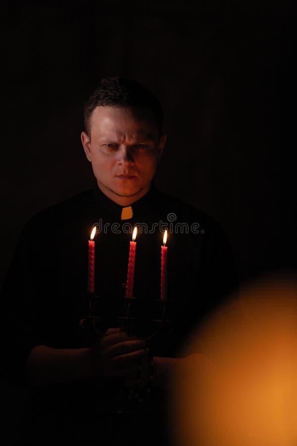 Stående av den stiliga katolska prästen eller pastorn med hundhalsbandet, mörker - röd bakgrund med tre röda stearinljus i handen royaltyfria bilder