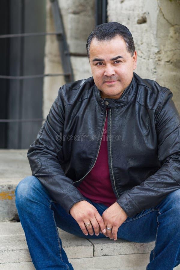 Stående av den stiliga latinamerikanska mannen som bär ett svart läderomslag arkivfoton