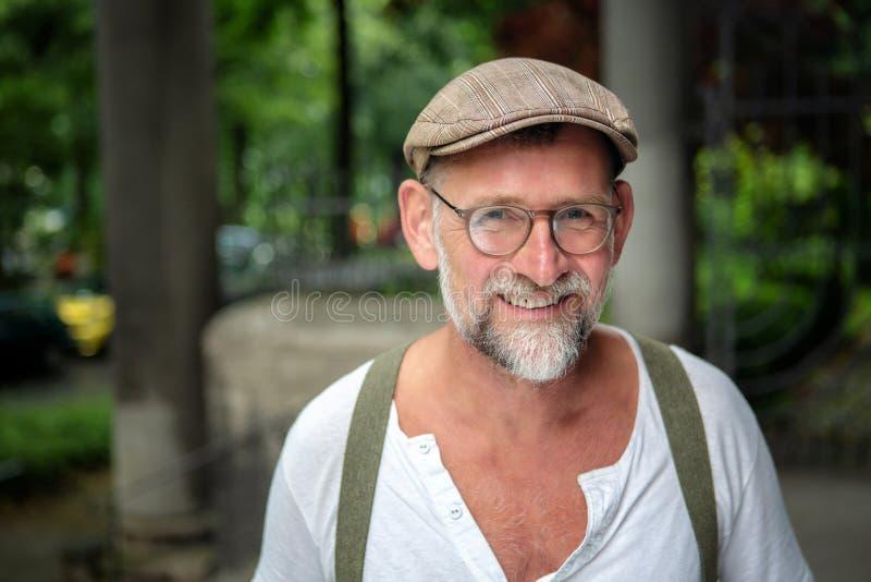 Stående av den stiliga le skäggiga mannen i hans 50-tal fotografering för bildbyråer