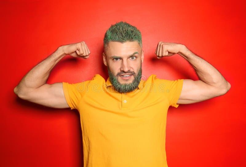 Stående av den stiliga mannen med färgat hår och att uppsöka visa muskler på färgbakgrund arkivfoton