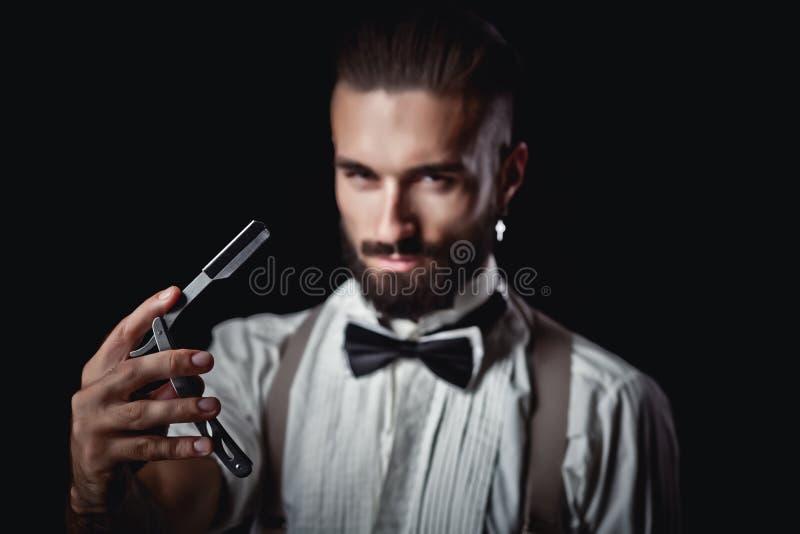 Stående av den stiliga mannen som poserar för fotograf i studion, farlig rakkniv, royaltyfria foton
