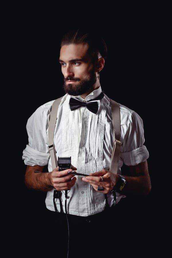 Stående av den stiliga mannen som poserar för fotograf i studion, rakkniv, barberare arkivbilder