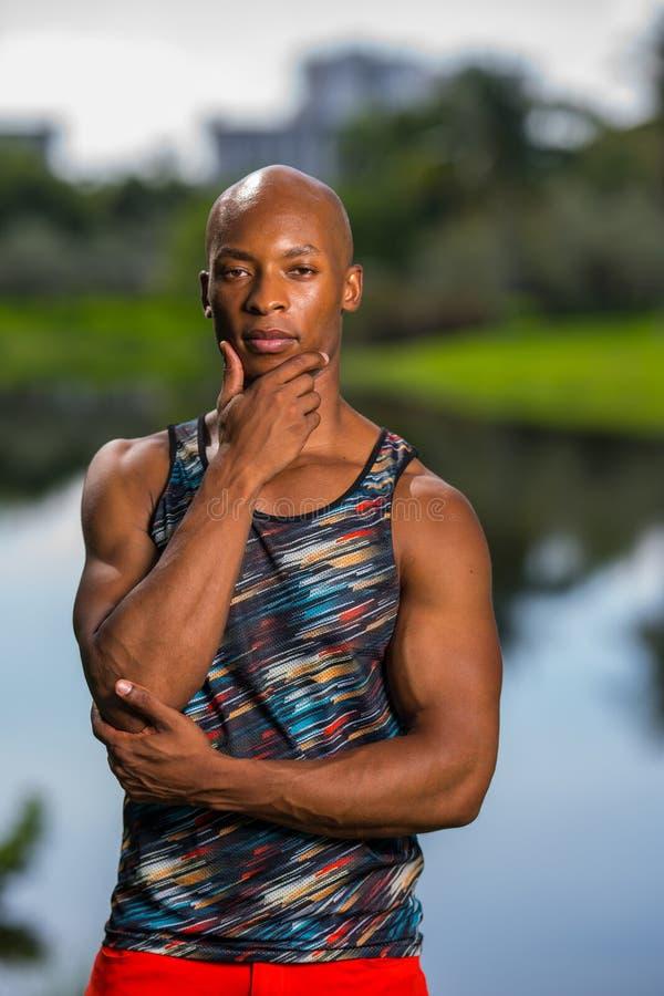 Stående av den stiliga mannen som poserar med handen under hakan Idrotts- person för afrikansk amerikan med en ärmlös tröjaskjort arkivbild
