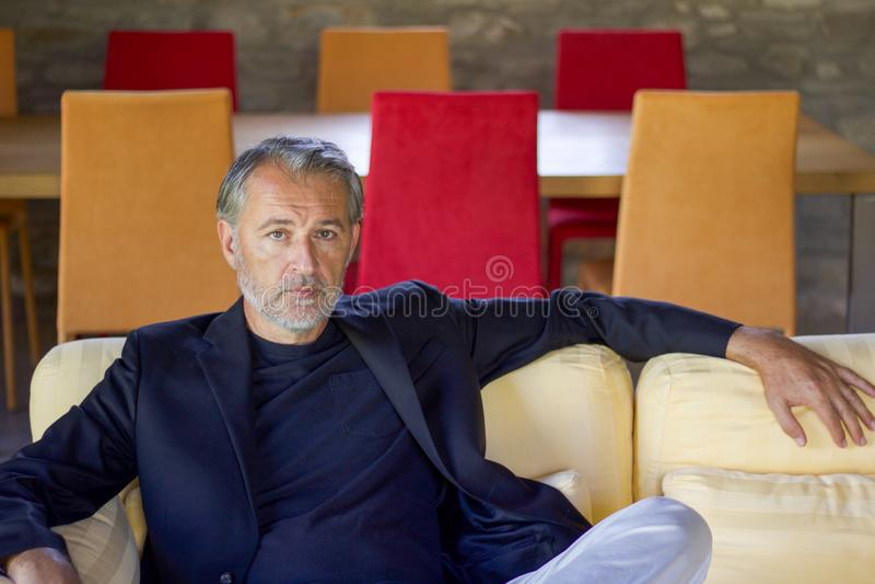 Stående av den stiliga mannen som sitter på en gul soffa i en vardagsrum royaltyfria bilder