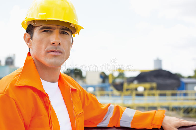 Stående av den stiliga mitt- vuxna mannen som bär skyddande workwear på konstruktionsplatsen royaltyfri fotografi