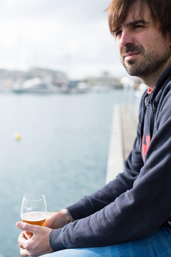 Stående av den stiliga skäggiga mannen med exponeringsglas av öl arkivfoton