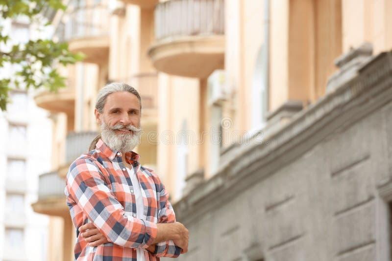 Stående av den stiliga skäggiga mogna mannen utomhus arkivbild