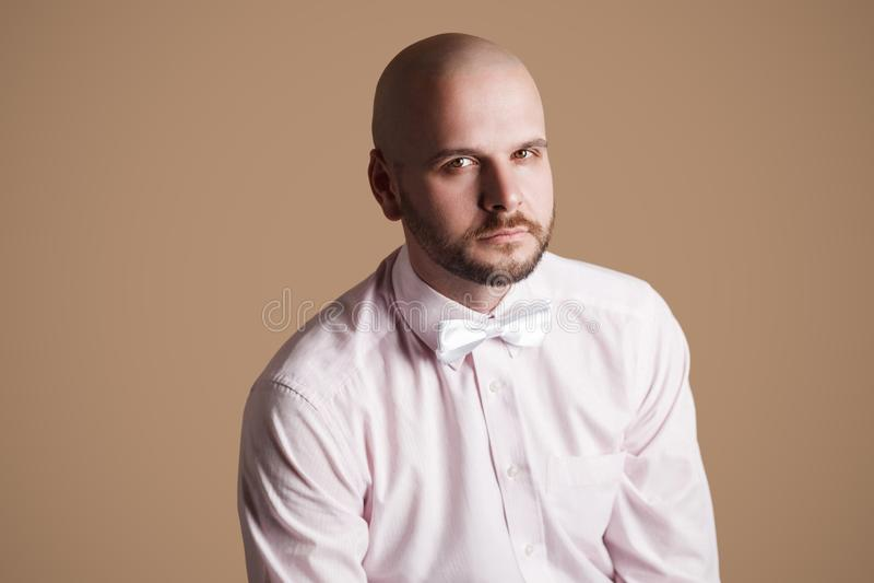 Stående av den stiliga skäggiga skalliga mannen i ljus - rosa skjorta och wh arkivfoto