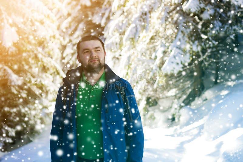 Stående av den stiliga skäggiga unga mannen i vinterskog royaltyfri bild