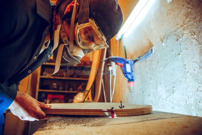 Stående av den stiliga snickaren som arbetar med skridskon på seminariet royaltyfri fotografi
