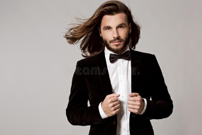 Stående av den stiliga stilfulla mannen i elegant svart dräkt royaltyfri bild