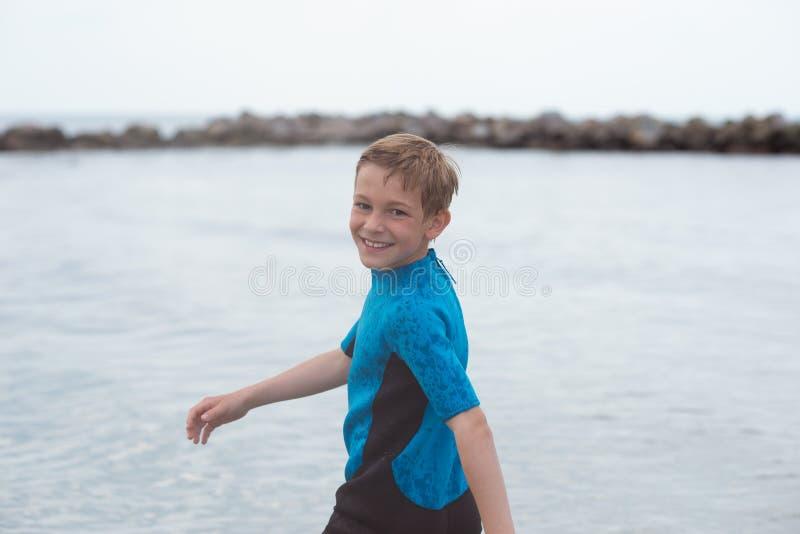 Stående av den stiliga tonåriga pojken som kör i neoprenebaddräkt i havet arkivfoto