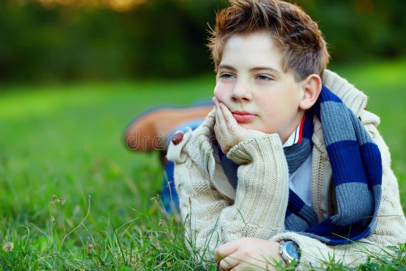 Stående av den stiliga tonåringen på grönt gräs arkivfoto