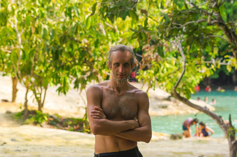Stående av den stiliga topless mannen med korsade armar framme av en sjöuntr träden royaltyfri bild