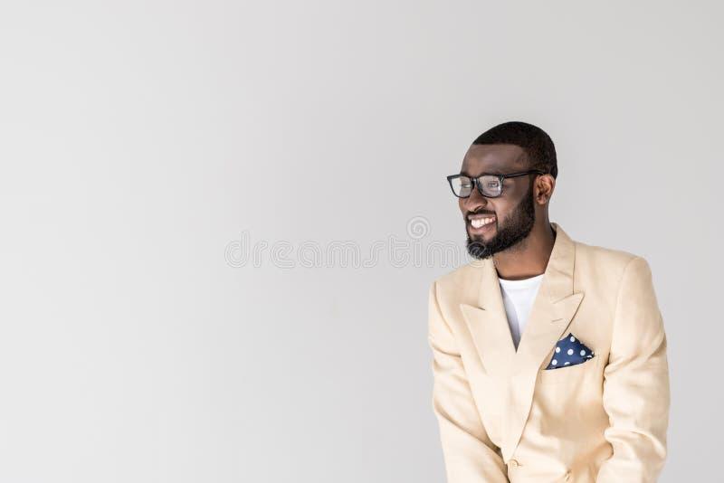 stående av den stiliga unga afrikansk amerikanmannen i glasögon som bort ler och ser arkivfoton