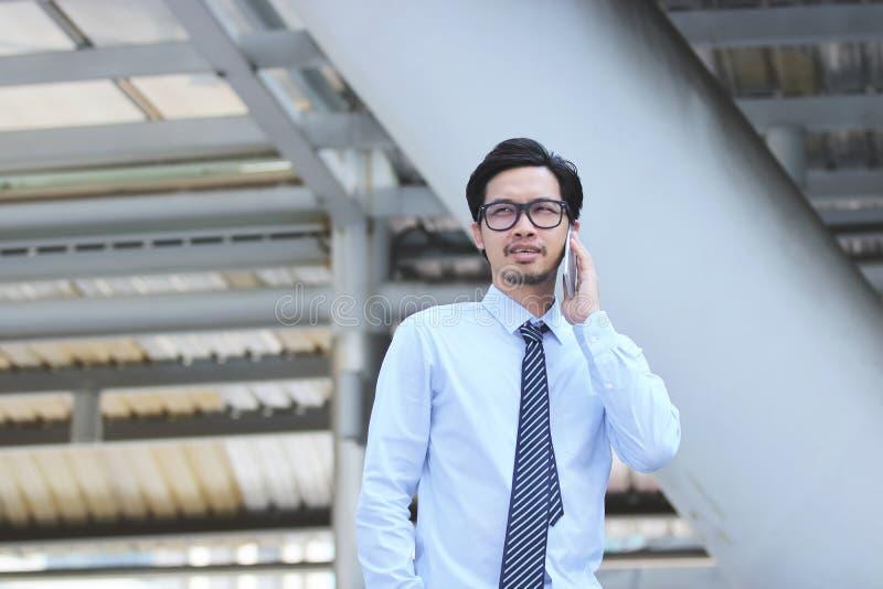 Stående av den stiliga unga asiatiska affärsmannen som talar på den smarta telefonen för mobil på trottoaren in i kontor arkivfoton