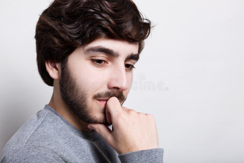 Stående av den stiliga unga fundersamma mannen med skägginnehavhanden på hakan som ser ner att tänka om något som är inportant ef royaltyfri foto