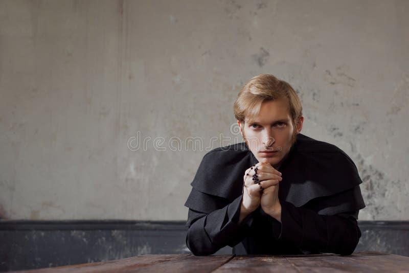 Stående av den stiliga unga katolska prästen som ber till guden Mörk stil, begreppstvivel royaltyfri foto
