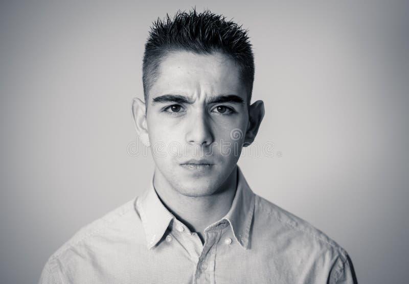 Stående av den stiliga unga mannen i neutrala pokeransiktsuttryck och mänskliga sinnesrörelser fotografering för bildbyråer