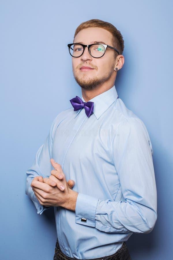 Stående av den stiliga unga mannen som bär i en skjorta och en fluga arkivfoto