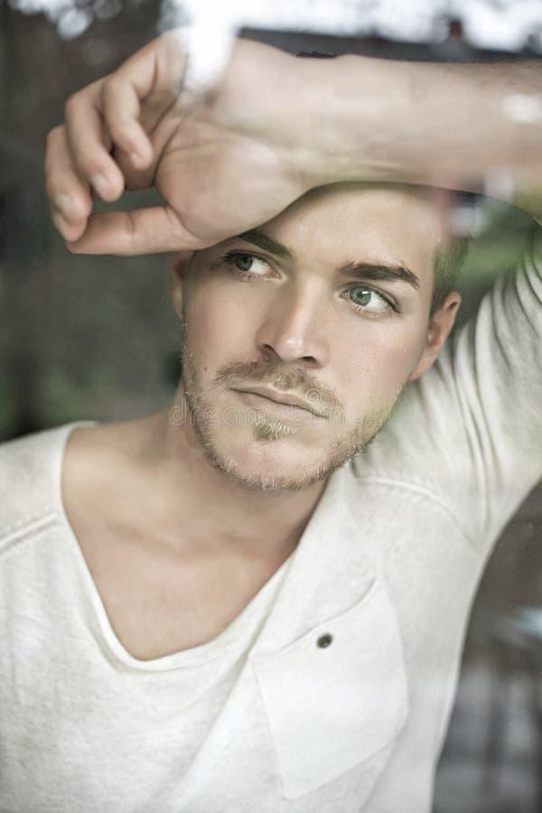 Stående av den stiliga unga mannen som ser till och med fönster royaltyfri fotografi