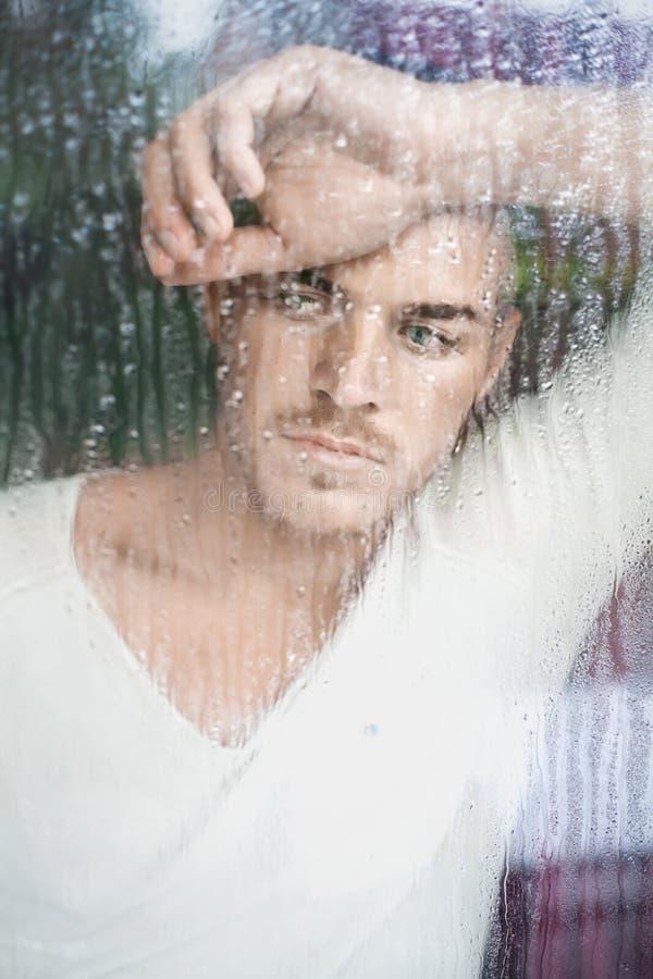 Stående av den stiliga unga mannen som ser till och med våt windo royaltyfri foto