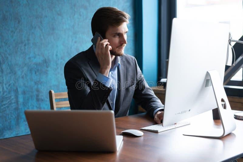 Stående av den stiliga unga mannen som sitter på kontorsskrivbordet med bärbar datordatoren och talar på mobiltelefonen Kommunika arkivbilder