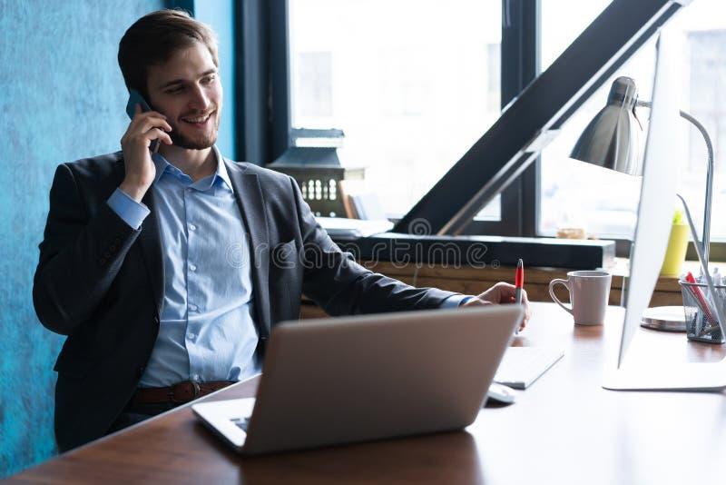 Stående av den stiliga unga mannen som sitter på kontorsskrivbordet med bärbar datordatoren och talar på mobiltelefonen Kommunika royaltyfri fotografi