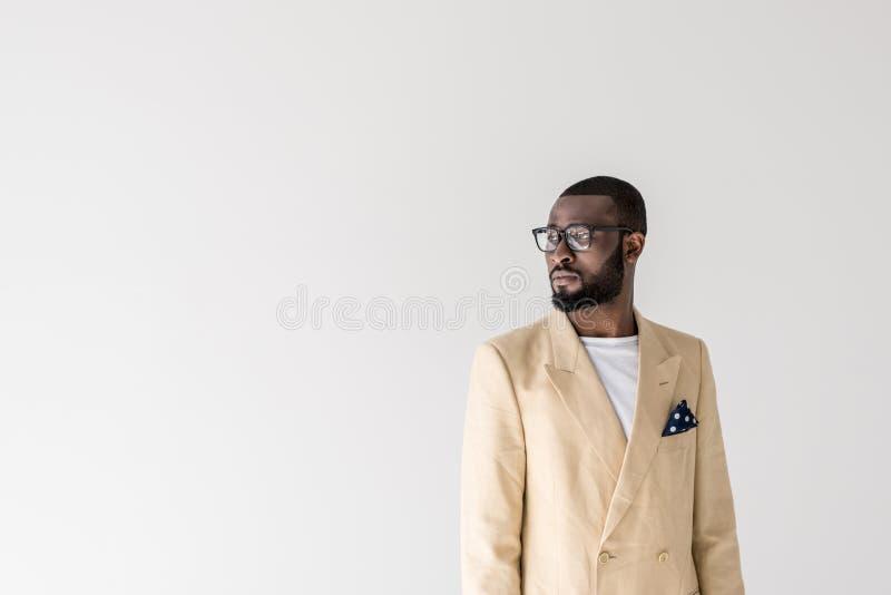 stående av den stiliga unga stilfulla afrikansk amerikanmannen i glasögon som bort ser royaltyfria bilder