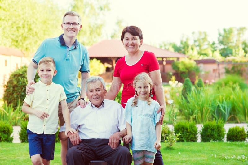 Stående av den stora lyckliga familjen med den gamla farfadern, hans dotter arkivfoto