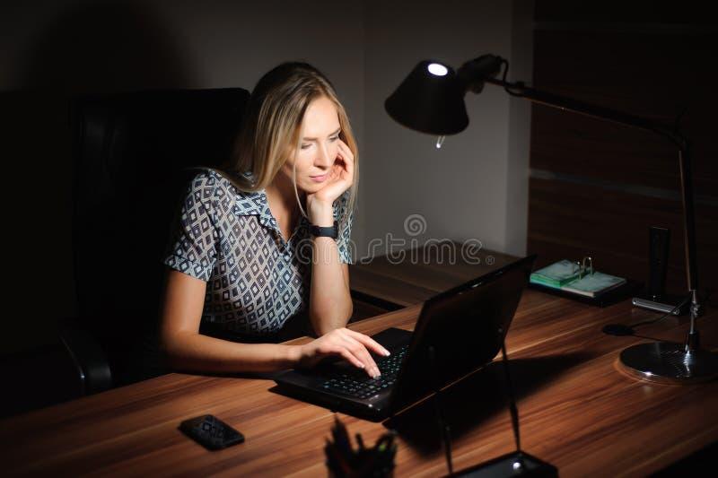 Stående av den stressade affärskvinnan som sitter på kontorsskrivbordet och tänker lösningen, medan arbeta sent framme av a fotografering för bildbyråer