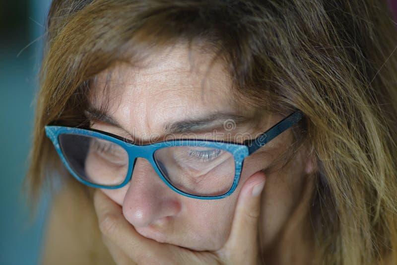 Stående av den stressade mogna kvinnan med handen på munnen som ner upp ser, slut Reflexion för datorbildskärmljus på framsida be fotografering för bildbyråer