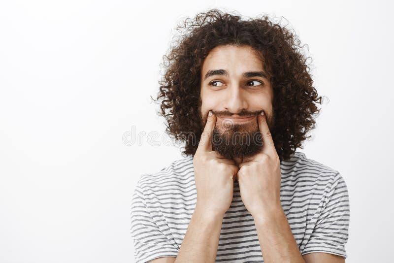 Stående av den stressade upprivna attraktiva skäggiga mannen med lockigt hår som drar leende med pekfingret och ser lämnad med royaltyfria bilder
