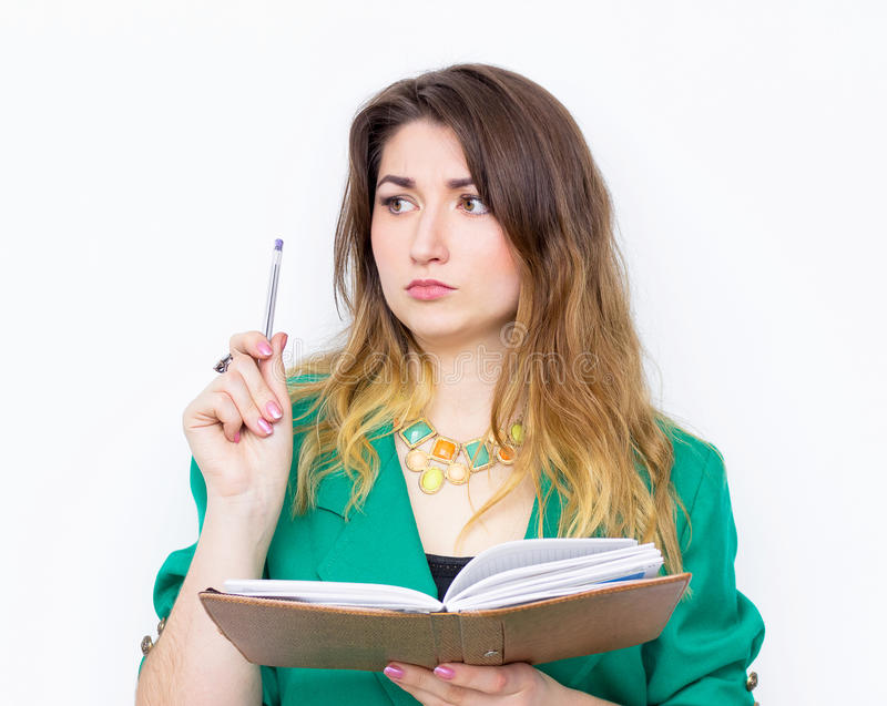 Stående av den tänkande affärskvinnan som bär i det gröna omslaget som är borttappat i tanke med pennan royaltyfri foto