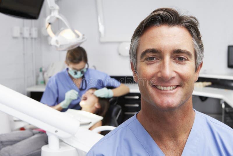 Stående av den tandsköterskaWith Dentist Examining patienten i bakgrund arkivfoton