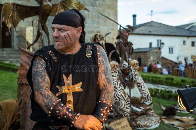 Stående av den tatuerade mannen som kläs som medeltida hovslagare i medeltida marknad av Puebla de Sanabria spain zamora royaltyfri foto