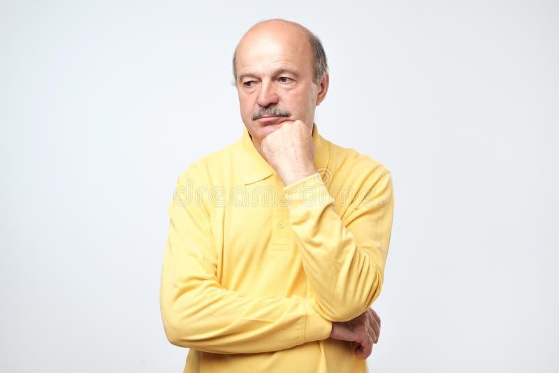 Stående av den tillfälliga mogna mannen i gul skjorta som tänker och ser förbryllad arkivbild