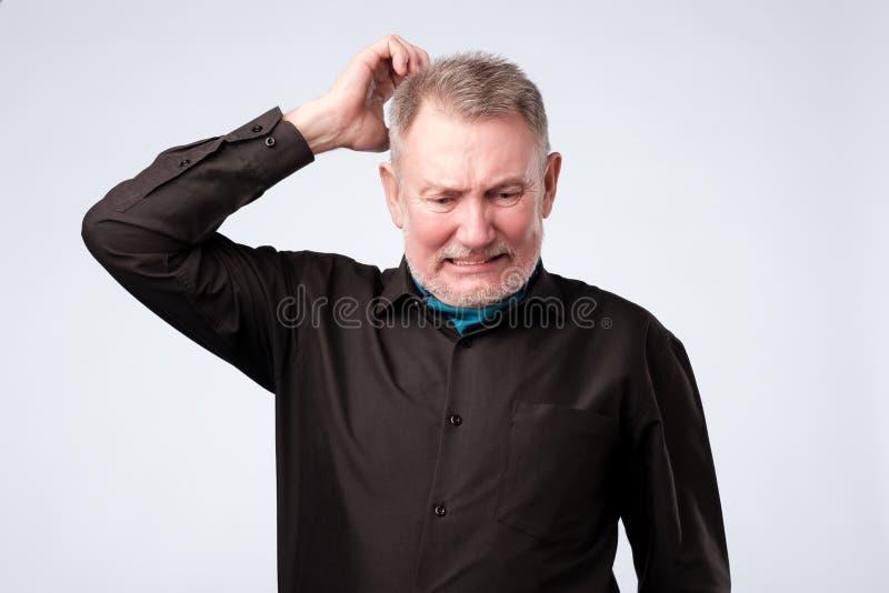Stående av den tillfälliga mogna mannen i svart skjorta som tänker och ser förbryllad arkivfoton