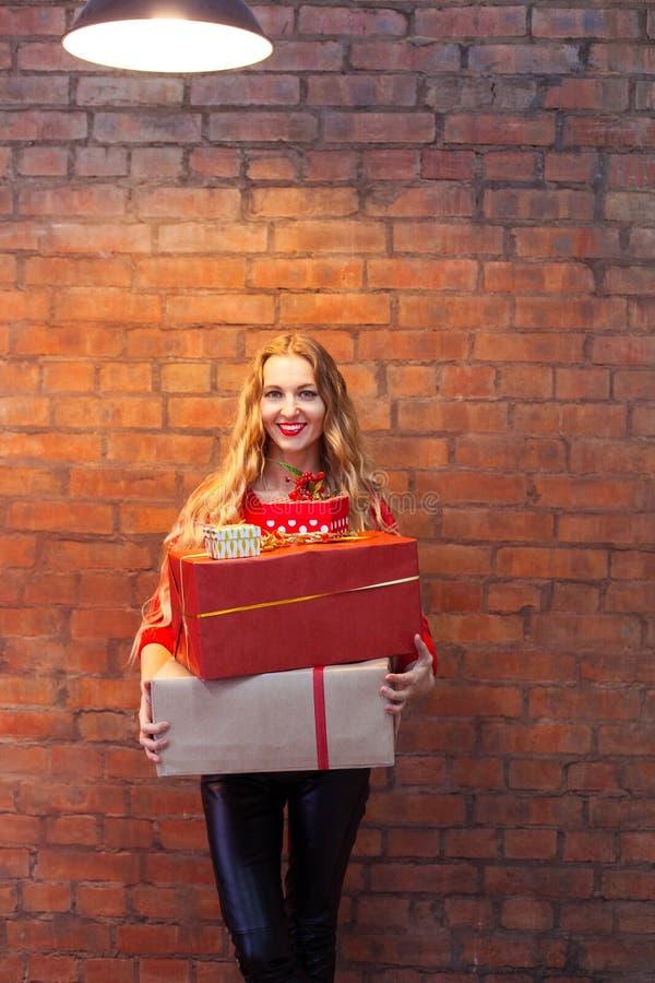 Stående av den tillfälliga unga lyckliga le asken för kvinnahållgåva igen arkivfoto