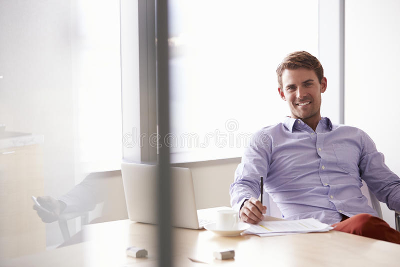 Stående av den tillfälligt klädda affärsmannen Sitting At Desk arkivbilder