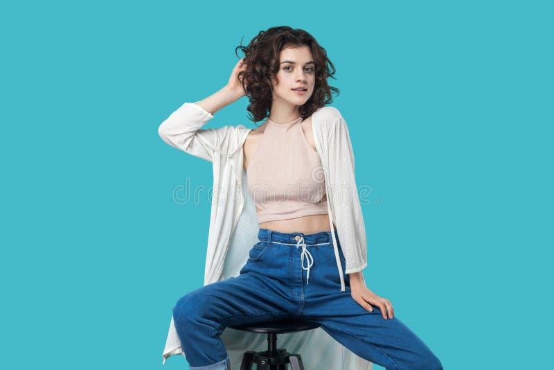 Stående av den tillfredsställda härliga unga brunettkvinnan i tillfällig stil som sitter på stol och poserar som modemodell och s royaltyfri bild