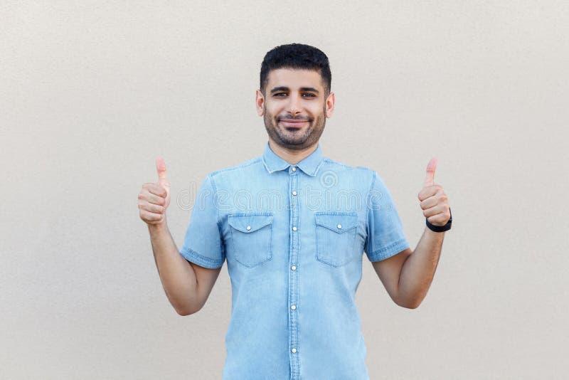 Stående av den tillfredsställda lyckliga stiliga unga skäggiga affärsmannen i blått anseende, le, tummar som gest och se för skjo arkivfoto
