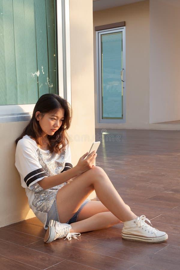 Stående av den tonåriga kvinnan med den allvarliga framsidan som ser och läser mes royaltyfri foto