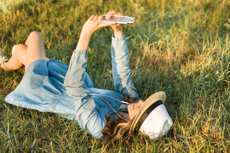 Stående av den tonårs- flickan 14 år gammalt ligga på gräset Flickan i klänninghatt, i hennes hörlurar rymmer en smartphone, lyss royaltyfri bild