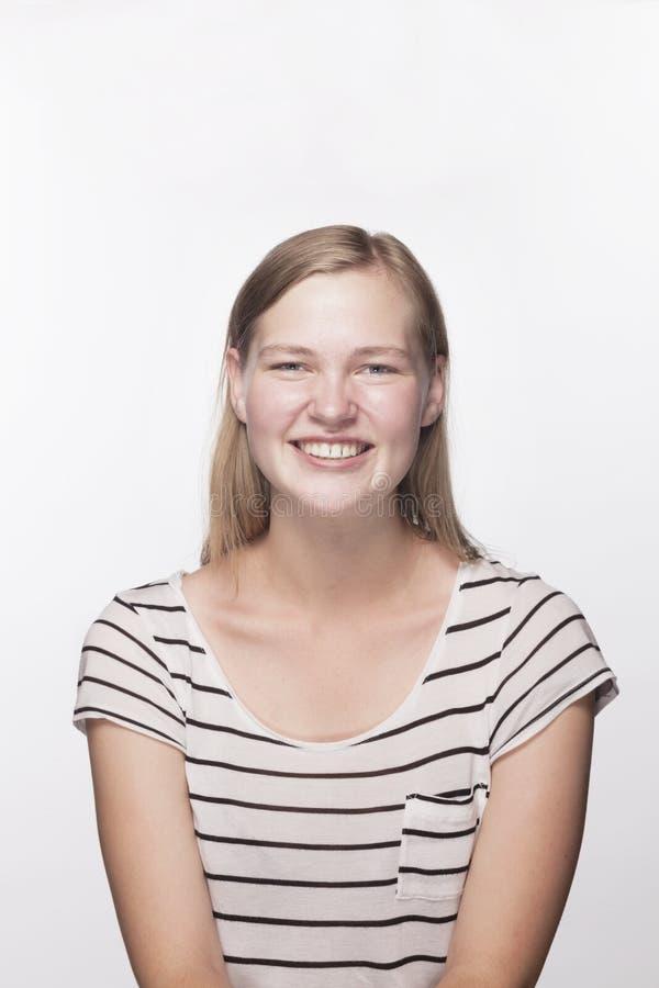 Stående av den tonårs- flickan med blont hår som ler, studioskott fotografering för bildbyråer
